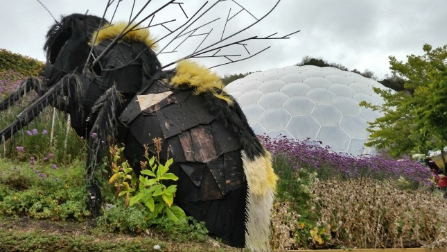a large bee sculpture in the foreground of a flower bed.A biome is in the background
