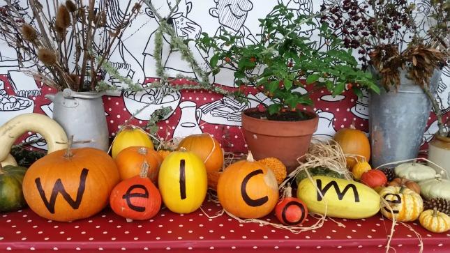 a pumpkin display with the words welcome written across 7 pumpkins