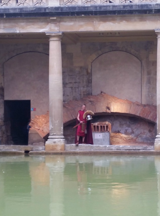 A customer Roman soldier actor walks around the main baths