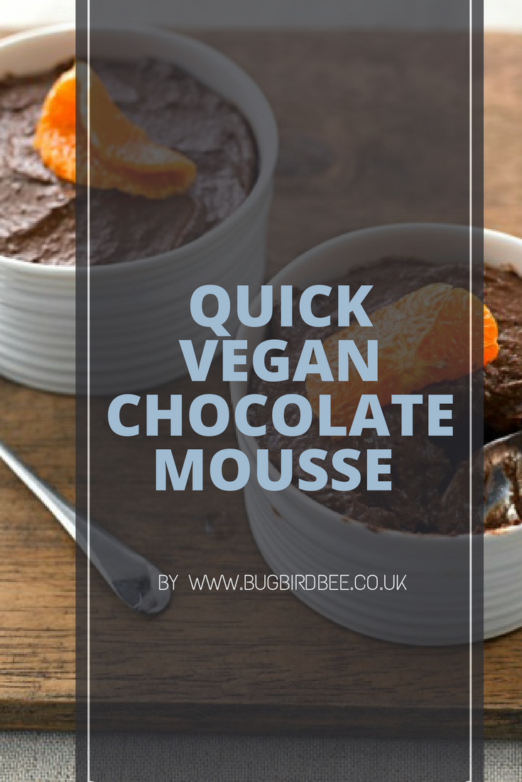 Two chocolate mousses in white pots decorated with with a single segment of Clementine. Text overlay-- quick vegan chocolate mousse