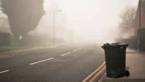 An empty Misty street with a green household bin