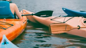 A close up of two kayaks and paddles floating on the water